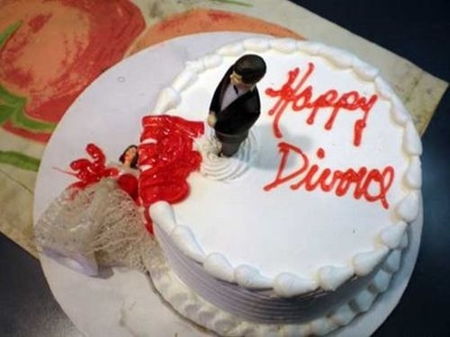 White divorce cake with bleeding bride cake topper knocked off cake